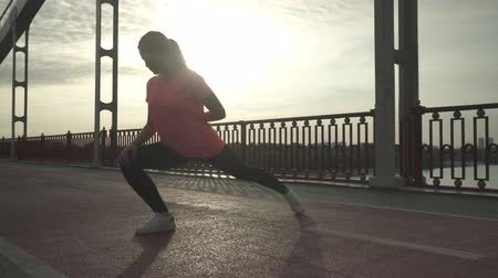 raises : The girl warm up before jogging outdoor. The lady spends time outdoor alone. The woman leads a healthy lifestyle. Female crouches and raises hands, preparing to run Stock Footage