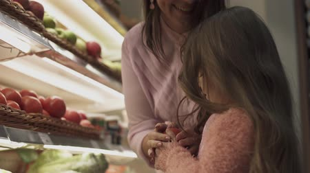 caixa : Little girl with mom in the supermarket. Daughter helps mom shopping in the store. Beautiful dark haired mother with a little daughter buying food at a grocery store