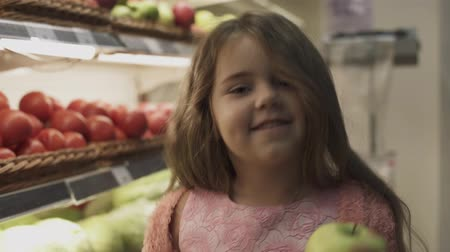 pokladna : Little smiling girl gets an apple from the shelf in the store. The girl kisses an apple and smiles. Happy little girl holding an apple in her hands. Dostupné videozáznamy