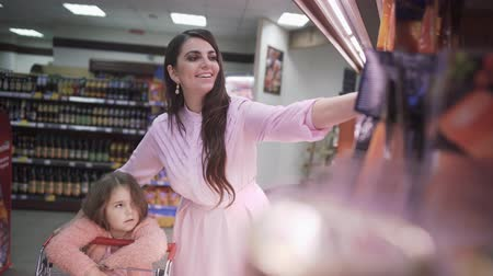 register : Little daughter helps mom shopping at the supermarket. Little girl with mom in the supermarket. Daughter helps mom shopping in the store. Beautiful dark haired mother with a little daughter buying food at a grocery store