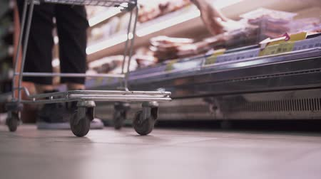 pokladna : A man puts products in the cart that pulls in the supermarket. Close-up of a cart on the background of the grocery shelf in the store Dostupné videozáznamy
