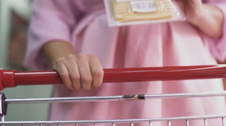 pokladna : Close-up of a female hand putting products into a trolley in a supermarket. Shopping at the grocery store.