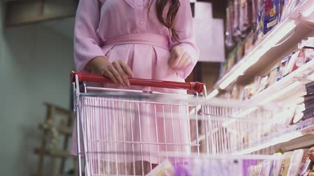 caixa : Female hand puts food into the cart near the grocery shelves in the supermarket. Shopping at the grocery store.