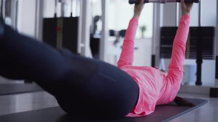 anexar : Female raise weight cttached to her legs and hands in the gym. Female is doing strength exsercises on legs in the gym standing on knees. Woman wants to be healthy and strong. Healthy lifestyle of young people Stock Footage