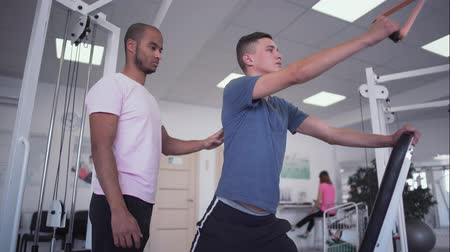 esportivo : African-american coach helps young guy to train. Young male is doing strength exercises. Teenager wants to be healthy and strong. Healthy lifestyle of young people