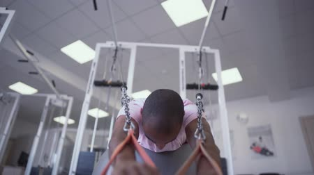esportivo : African American guy doing exercise on the simulator lying on therapy ball. Pediatric Physical Therapy Vídeos