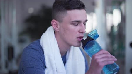 ivászat : The male is drinking water in the gym. Young man with white towel on his neck is resting after training. The man wants to be healthy and strong. Healthy lifestyle of people Stock mozgókép