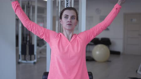 pull out : Pretty female in pink jacket raises weight in the gym. Woman wants to be healthy and strong. Healthy lifestyle of young people