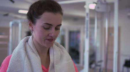 ivászat : The female is drinking water in the gym. Young woman rubbing sweat from her forehead. The lady is resting after training. Healthy lifestyle of people Stock mozgókép