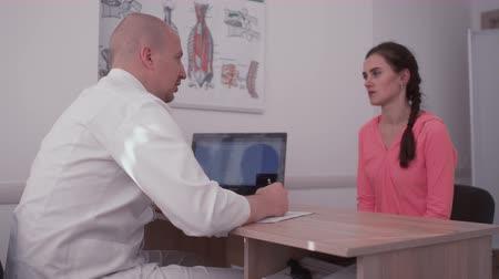 cirurgia : Osteopath is talking with his patient in his office. sitting at the table. The man ask woman questions about her back. Woman wants to be healthy and strong. Patient and doctor relationship