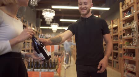 şarap kadehi : Pretty girl seller offers wine to the visitor. A bearded guy with tattoos on his arm wants to buy good wine at a liquor store. Stok Video