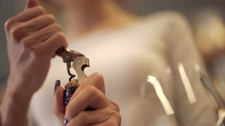 tasting : Girl gets a cork with the help of corkscrew. Wine glass is standing near. Keeping of alcoholic drinks Stock Footage