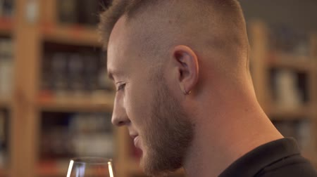 tasting : Portrait of handsome male smelling wine in the glass close up in profile Man admires alcohol drink. Customer is in alcohol shop