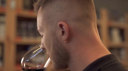предназначенный только для мужчин : Portrait of handsome male sniffing wine in the glass close up in profile. Man tastes alcohol drink and admires it. Customer is in alcohol shop