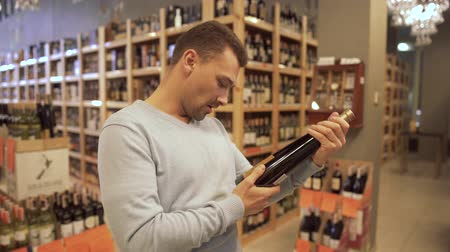 realization : Handsome man studying the inscriptions on the bottle. Wine bottles are standing on wooden shelves. Keeping of alcohol drinks. Customer is in alcohol shop