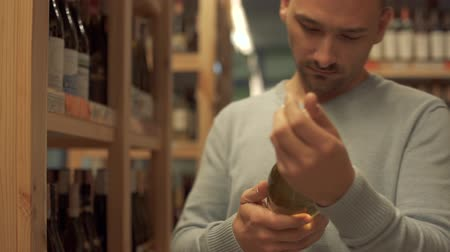 realization : Handsome man studying the inscriptions on the bottle. Wine bottles are standing on wooden shelves. Keeping of alcohol drinks. Customer is in alcohol shop.