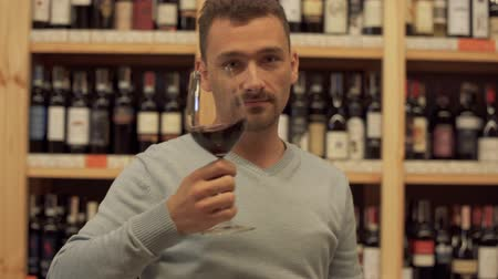 realization : Portrait of man drinking red wine close up. Man puts his glass very close to camera and then tastes alcoholic drink. Cheerful male with beard looks in camera Stock Footage