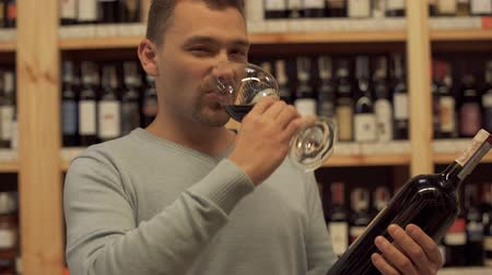 realization : Handsome male is smelling wine in the glass. Man is holding bottle in the hand. Man tastes alcoholic drink and likes it. Customer is in alcohol shop