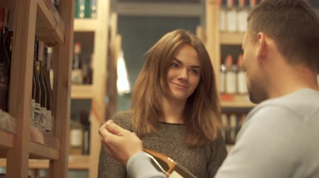 realization : Handsome man is holding bottle of wine. Customers choosing drink in alcohol shop. Male and female have discussion about alcohol Stock Footage