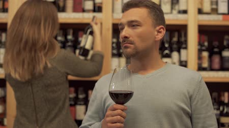 realization : Portrait of handsome man standing with glass of red wine in alcohol shop close up. Woman in the background is choosing wine bottle. Place with lot of alcohol drinks.
