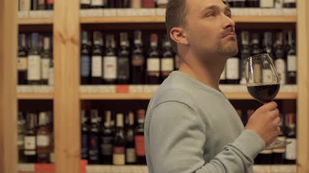 realization : Portrait of handsome man standing with glass of red wine in alcohol shop close up. Woman in the background is choosing wine bottle. A lot of alcoholic beverages on wooden shelves.