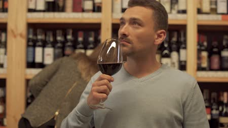decisões : Portrait of handsome man standing with glass of red wine in alcohol shop close up. Woman in the background is choosing wine bottle. Place with lot of alcohol drinks.