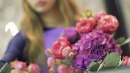 florista : Florist makes a bouquet at the flower shop. Female hands picking flowers in a bouquet. Close up. Stock Footage