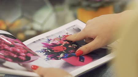 буклет : Close up of female hand with a red manicure. Female fingers gliding through the floristic booklet.