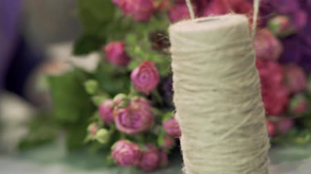 kötés : Rope is unwound on the reel. Coil of twine on the background of a bouquet of roses. Focus moves from the spool with the rope to the bouquet.