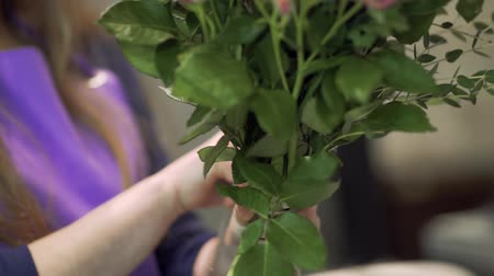 designing : Woman florist binds a bouquet of flowers with twine. Florist prepares a flowers bouquet for sale. Stock Footage