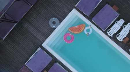 demirli : View from the top of the pool with bright colored inflatable circles. A top view of the pool with multicolored inflatable circles and sun chairses standing by the pool.