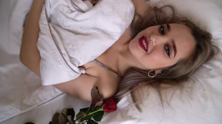 yatak kıyafeti : Portrait of young smiling lady with bright makeup lying in bed close up. Female winks looking at the camera. Red rose is laying near. Female winks looking at the camera. The camera is spinning slowly