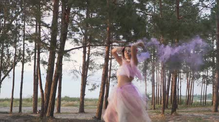 ağaç gövdesi : Beautiful girl with bright makeup in a pink dress dancing with smoke bombs on the background of pine trees.
