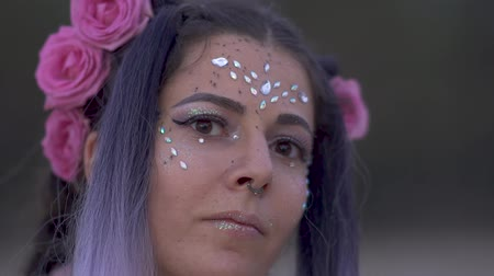 delici : Close up portrait of sensual young woman with sparkling makeup and a flower hairstyle. Slow motion.
