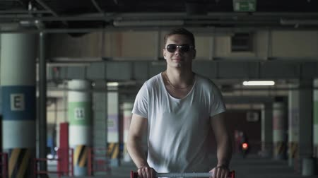 perseguição : Happy man in sunglasses and white t-shirt is walking in the underground parking lot