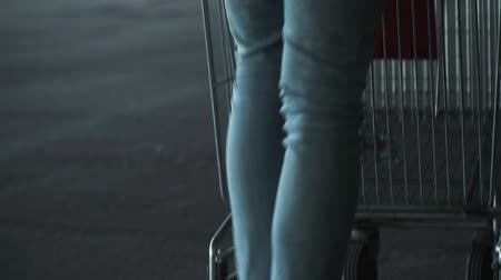 mercearia : Rear view of a man in dark sneakers with light jeans and a white jacket pushing a grocery cart in front of him in the parking lot.