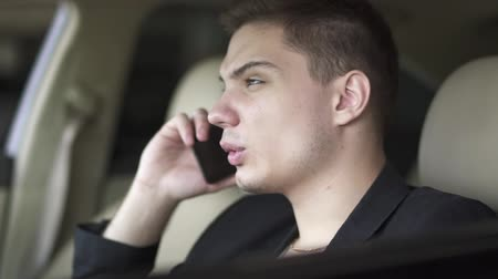 limusina : Portrait of young man who is chewing gum and talking by cell phone in the car close up. Leisure of rich confident businessman Archivo de Video