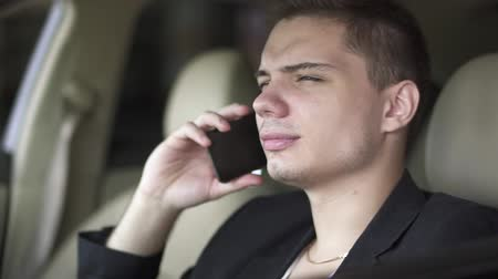limuzína : Portrait of young man who is chewing gum and talking by cell phone in the car close up. Leisure of rich confident businessman Dostupné videozáznamy
