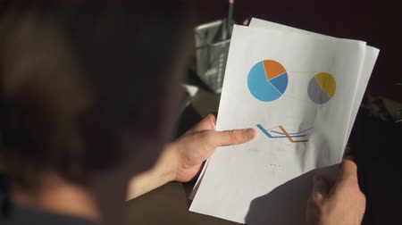 amendment : Businessman studies graphics and makes planned adjustments for the future holding reports with graphs close-up Stock Footage