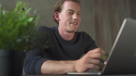 téma : Smiling young blond man sitting at computer and typing at laptop messages thinking about topic.