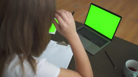 gadjet : Secretary negotiates online using the Internet and a laptop with a green screen standing on the table at her workplace