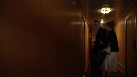 megérkezik : Nice dressed man and woman enter the room. Beautiful couple came to hotel. People walk in narrow corridor