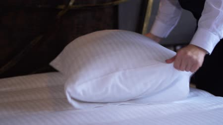 administrador : Hotel cleaning lady straightens a pillow in a small, cozy hotel room.