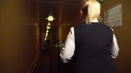 portaretrato : Cute maide with trolley walks in the hotel corridor. Archivo de Video