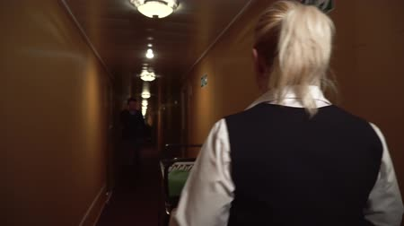 cleaning equipment : Maid rolls a trolley down the hall in the hotel and greets a man walking towards. Stock Footage