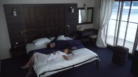arrive : Man and woman simultaneously falls on bed in hotel from different sides. Adult couple is tired after travel, they are resting in room with large window Stock Footage
