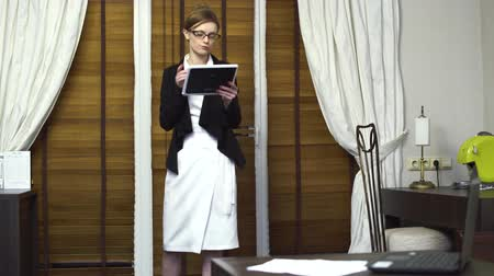 строгий : Business woman in a business suit walks around the office looking at current information on her tablet.
