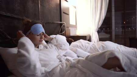 álom : Adult woman lays at the bed and puts sleep mask on her face preparing to sleep. Her husband is sleeping near. Couple rest in modern hotel room