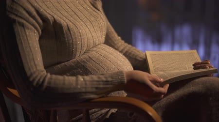 sem camisa : Pregnant woman is reading the book, sitting in rocking chair in dark room. Leisure of lonely woman who is waiting a baby Stock Footage