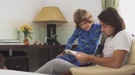 compreensão : Older brother reading a book to his younger brother. Brothers in sleepwears sitting in a chair discussing what they read in the morning Vídeos